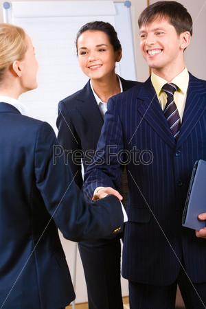 Улыбающийся молодой мужчина здоровается с деловой женщиной