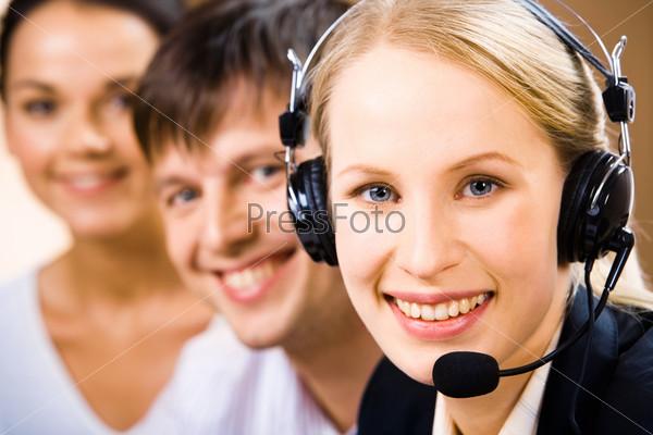 Диспетчер горячей линии с улыбкой смотрит в камеру на фоне своих коллег