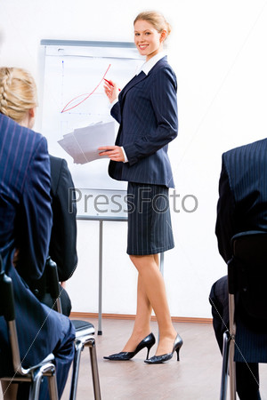 Успешная бизнес-леди выступает перед аудиторией с презентацией нового продукта