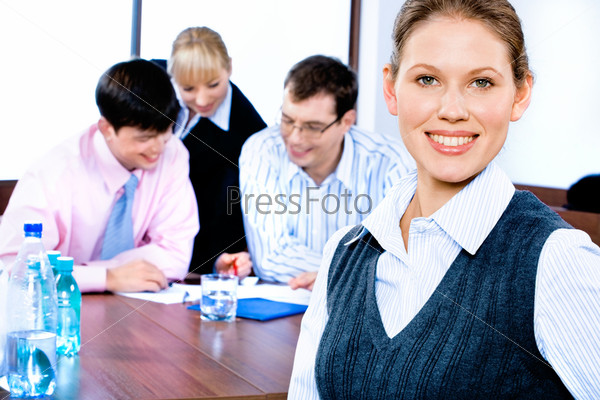 Довольная сотрудница стоит на фоне своих коллег