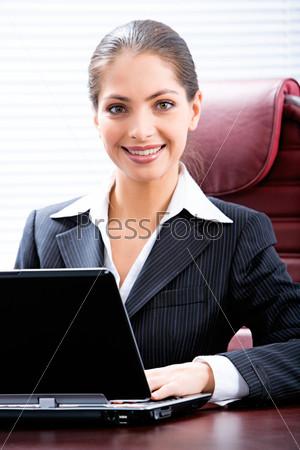Деловая начальница сидит за рабочим столом и улыбается