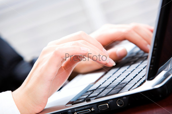 Крупный план женских рук за ноутбуком