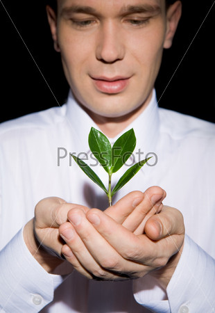 Мужчина заботливо смотрит на росток в его руках