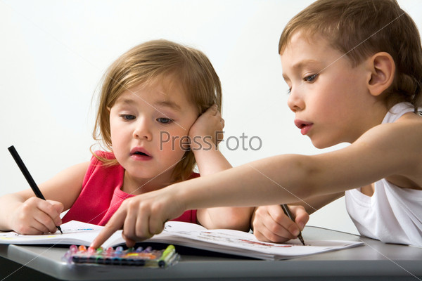 Careful brother shows to his smaller sister the color of felt-tip pen which is better for her drawing