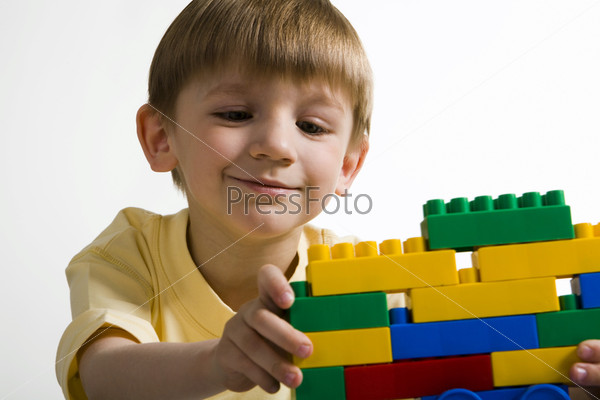 Isolated on white smiling boy in yellow t-shirt building with enthusiasm a construction