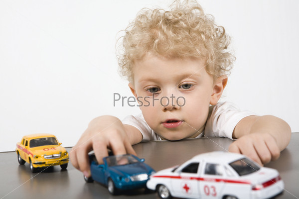 Isolated on white curly blond boy playing with cars on the gray table