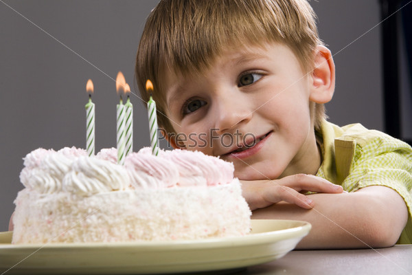 Happy blond boy with birthday cake looking at the candles