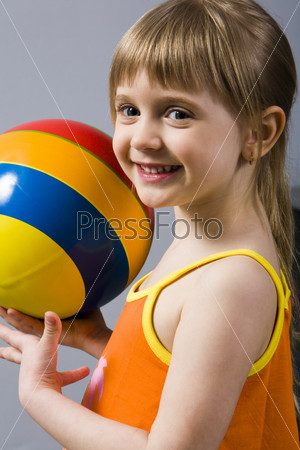 on gray smiling blond girl with multicolored ball