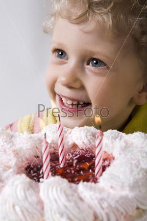 Мальчик с белыми кудрями собирается задуть свечи на торте