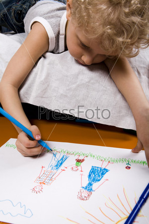 Curly blond boy lying on the bed drawing the picture of his family