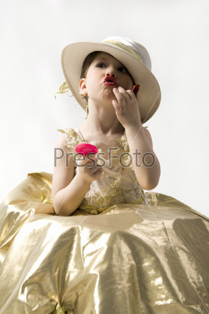 Isolated on white sweet brunette little girl in light goldish dress and white hat making up her lips