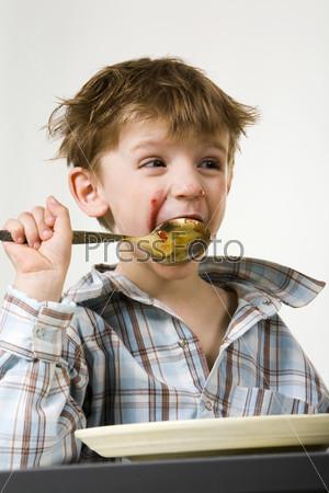 Лохматый и чумазый мальчик ест большой ложкой