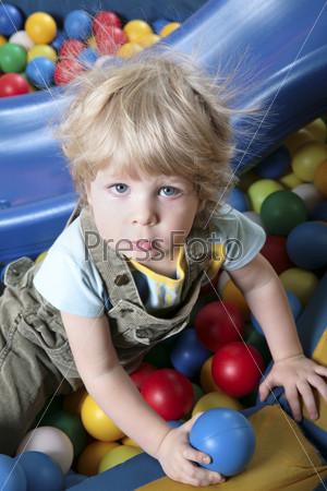Симпатичный мальчик с белыми волосами сидит в цветных шарах
