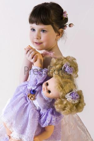 Маленькая темноволосая девочка в розовом платье держит в руках куклу