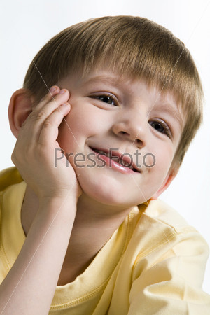 on white smiling blond boy in yellow t-shirt
