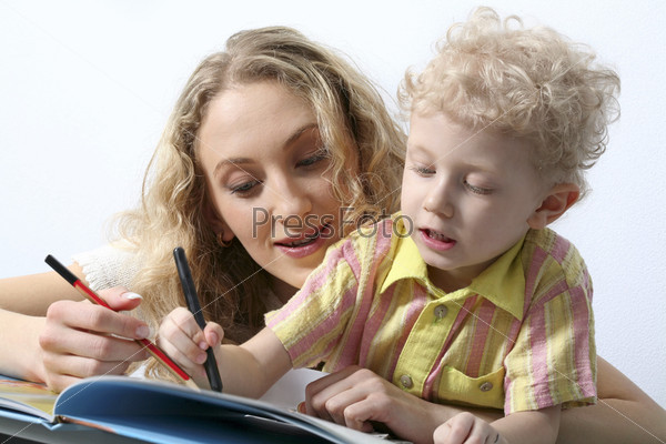 Isolated on white beautiful curly blond mother and her smart son reading a book together