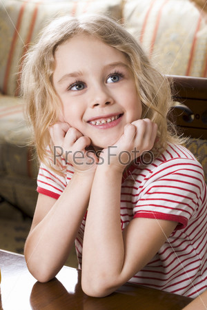 Smiling blond girl in stripe t-shirt sitting at the coffee table