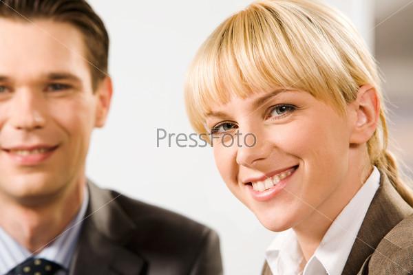 Успешная блондина смотрит в камеру с улыбкой