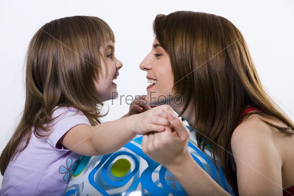 Smiling beautiful brunette mother and her pretty daughter playing with big ball