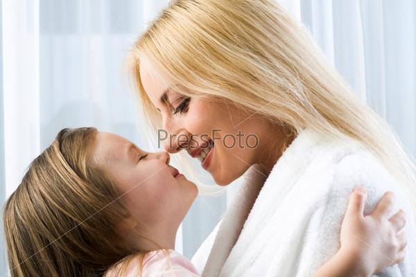 Светловолосая девочка обнимает маму и тянется ее поцеловать