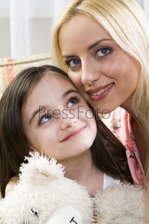 Smiling beautiful blond mother caring for her daughter holding her beloved bear