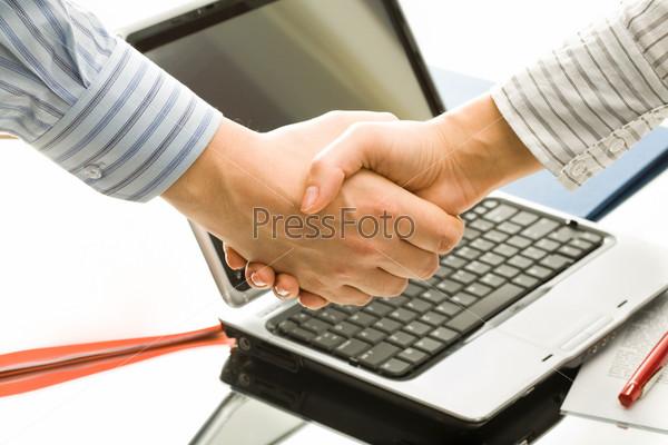 Крупный план мужского рукопожатия на фоне ноутбука