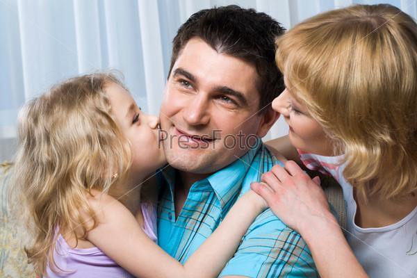 Фотография на тему Девочка, похожая на ангела, целует счастливого папу, которого обнимает жена