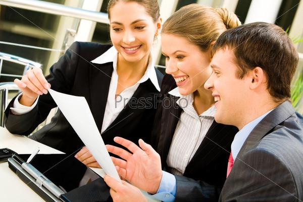 Сотрудники офиса изучают документ и улыбаются