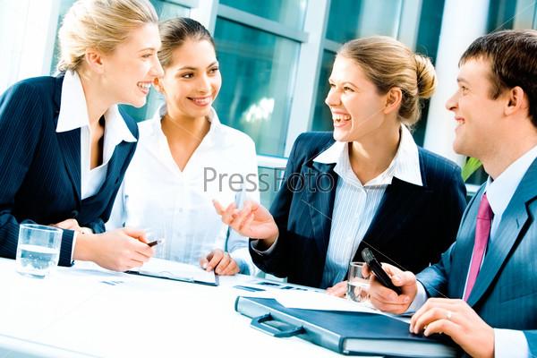 Фотография на тему Офисный персонал разговаривает и смеется сидя за столом