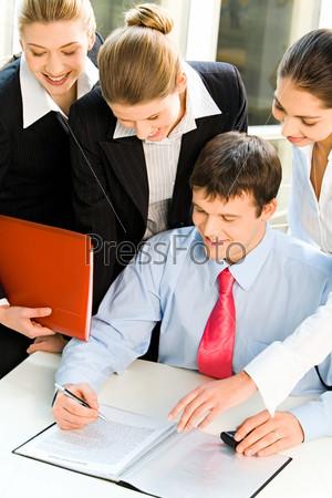 Три привлекательные девушки склонились над мужчиной сидящим за столом