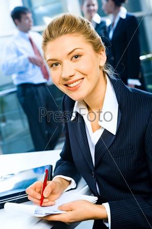 Фотография на тему Довольная секретарша сидит за письменным столом и улыбается