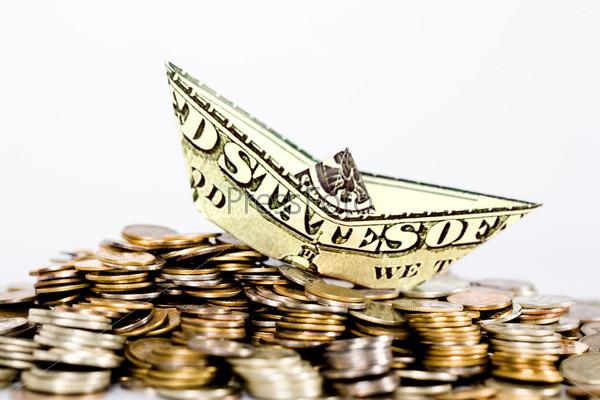 Американская денежная банкнота в виде кораблика на куче блестящих монет