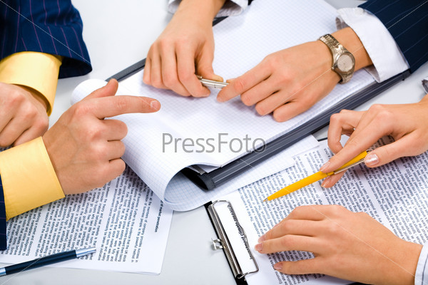 Руки трех бизнесменов лежащие на документах
