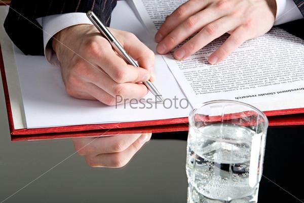 Бизнесмен сидящий над раскрытым документом за столом