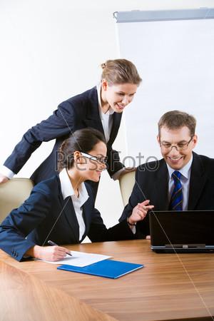 Сотрудники в кабинете начальника смотрят в ноутбук и улыбаются