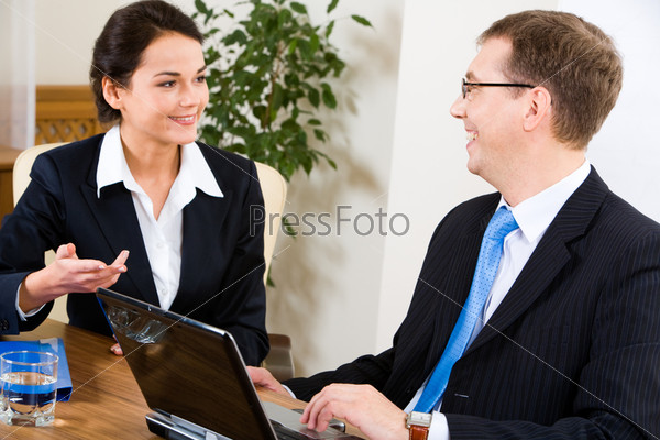 Коллеги общаются между собой сидя за рабочим столом