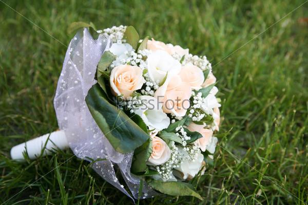 Букет из белых лилий и розовых роз лежит на зеленой траве