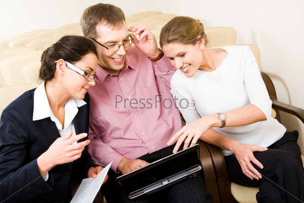 Успешные молодые люди улыбаясь смотрят в ноутбук