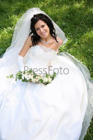 Фотография на тему Невеста с букетом цветов сидит на зеленой траве