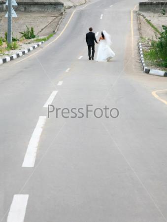 Новобрачные гуляют по асфальтовой дороге