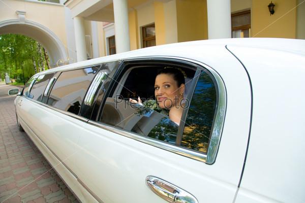 Счастливая невеста выглядывает из окна белого лимузина