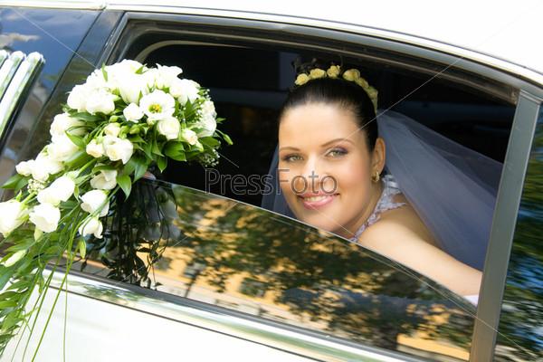 Счастливая невеста с букетом белых роз выглядывает из окна лимузина