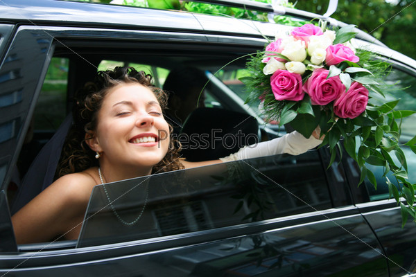 Счастливая невеста с закрытыми глазами  в лимузине держит в руке букет роз