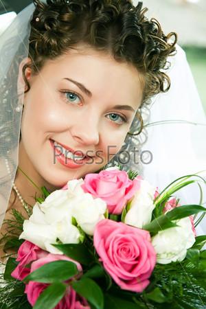 Молодая невеста смотрит в камеру и улыбается