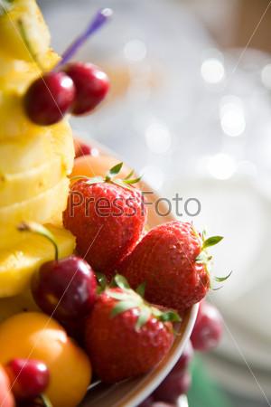 Сочные ягоды клубники и вишни на тарелке с кусочками ананаса