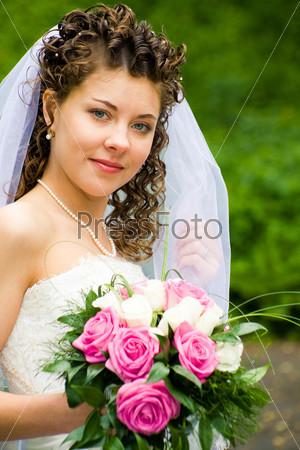 Красивая невеста с букетом роз в руках