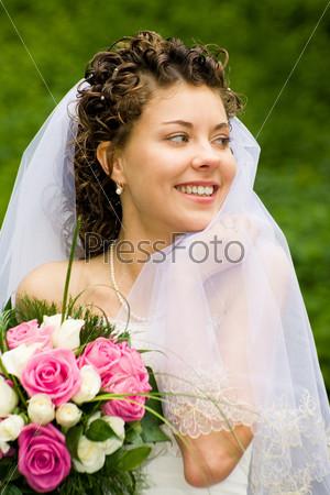 Очаровательная невеста улыбается и держит в руках букет