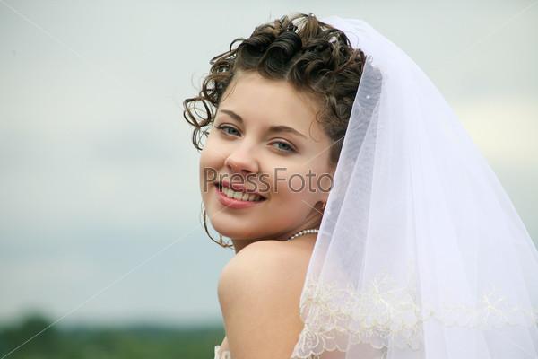 Счастливая невеста стоит на фоне неба и улыбается