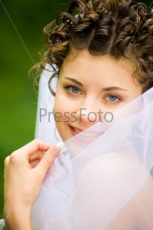 Очаровательная невеста улыбается, прикрывая лицо фатой