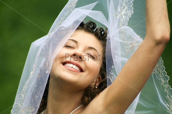 Счастливая девушка в свадебном платье с закрытыми глазами